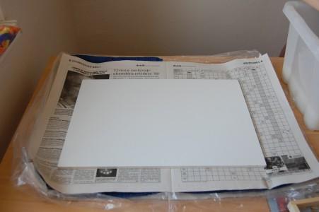 na vrstvu novin dáme desku a na ni utěrku